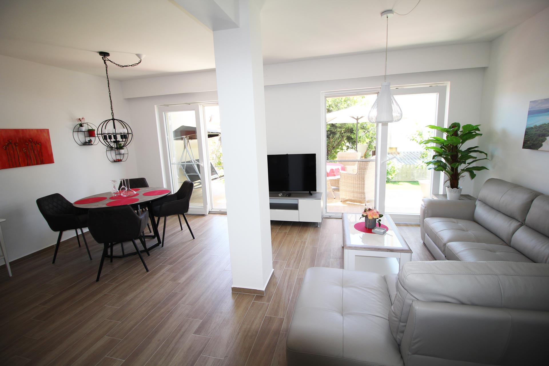 Ferienwohnung im Erdgeschoss - Wohnzimmer mit Couch und TV