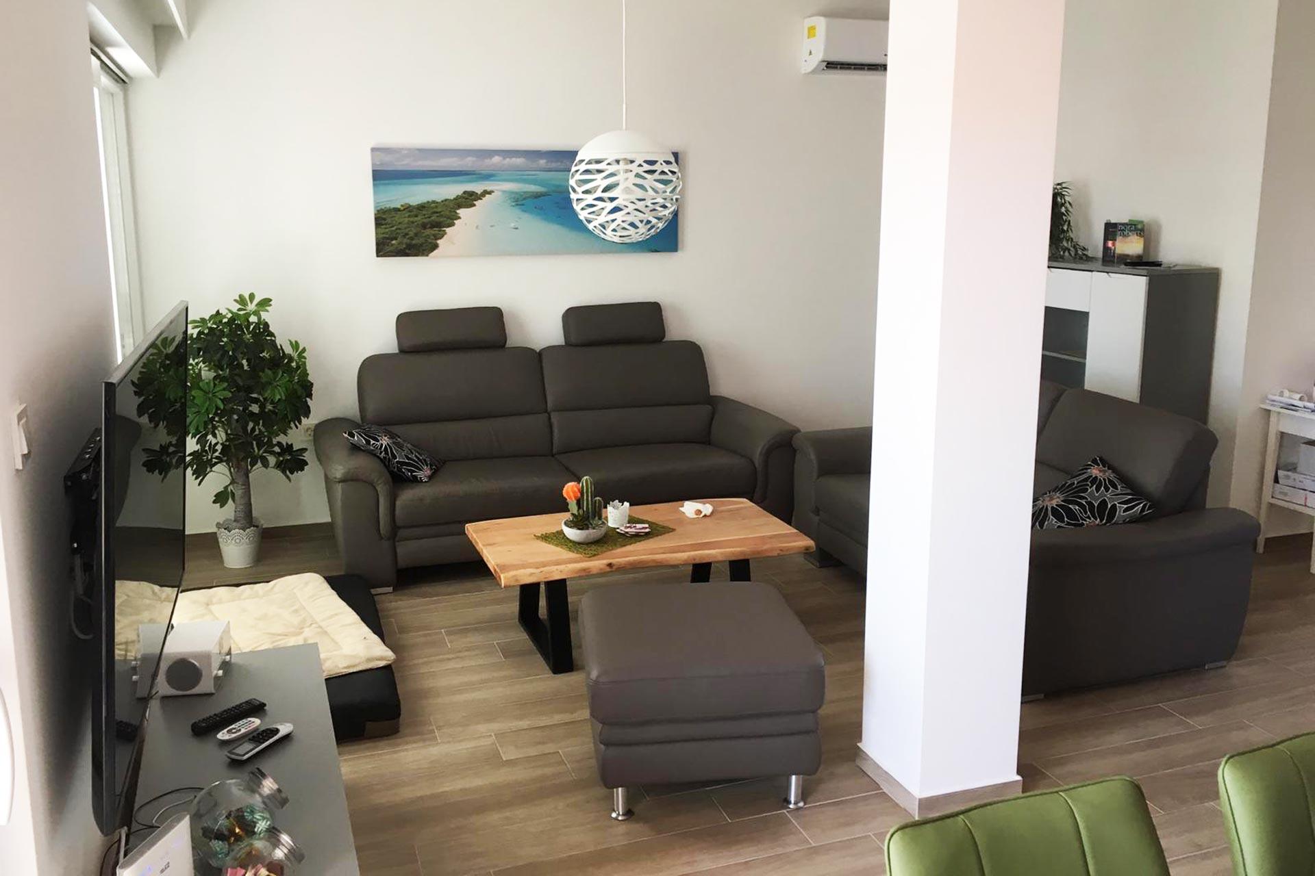 Ferienwohnung im Obergeschoss - Wohnzimmer mit Couch und TV